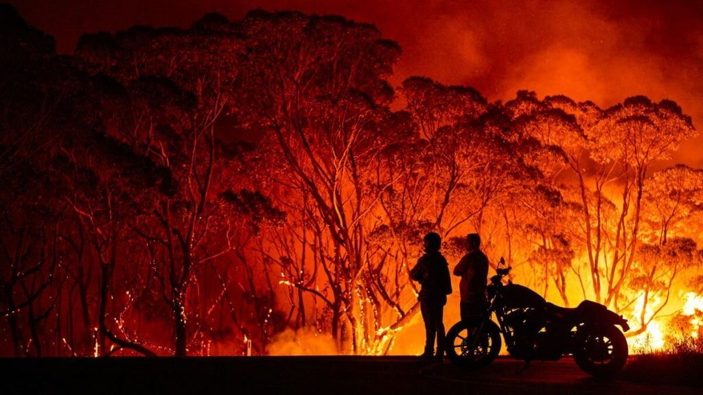 Residents look on as flames burn through bush in Lake Tabourie, Australia